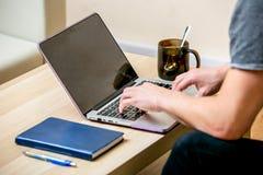 Geconcentreerde jonge mens met glazen die aan laptop in een huisbureau werken Type op een toetsenbord en rollentekst op de verton royalty-vrije stock foto's
