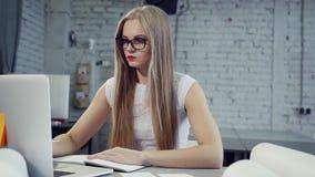 Geconcentreerde jonge vrouw die aan moderne laptop en het schrijven teksten werken stock footage