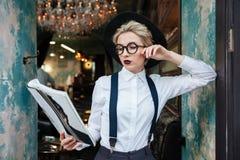 Geconcentreerde jonge vrouw die en tijdschrift in koffie bevinden zich lezen Stock Afbeeldingen