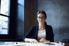 Geconcentreerde jonge vrouwelijke ontwerper in eyewear royalty-vrije stock afbeeldingen