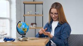 Geconcentreerde jonge vrouwen tellende muntstukken van glaskruik stock video