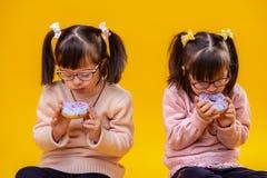 Geconcentreerde jonge zusters met wanorde gekleurd genieten van donuts stock foto's
