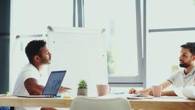 Geconcentreerde mannelijke collega's die in het bureau zitten stock videobeelden