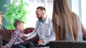 Geconcentreerde mannelijke pediater in witte laboratoriumlaag die stethoscoop met behulp van aan kindpatiënt stock videobeelden
