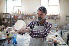 Geconcentreerde mannelijke pottenbakker die zijn verwezenlijking voor gebreken onderzoeken stock fotografie