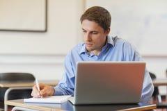 Geconcentreerde mannelijke rijpe student die zijn notitieboekje voor het leren gebruiken Stock Foto's