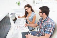 Geconcentreerde medewerkers die laptop en becijferaar met behulp van Stock Foto