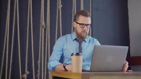 Geconcentreerde mens die PC met behulp van bij een koffie stock footage