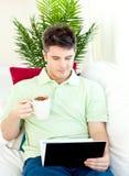 Geconcentreerde mens die zijn laptop het drinken koffie gebruikt Royalty-vrije Stock Foto