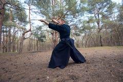 Geconcentreerde mens met een Japans zwaard, een katana Brede hoek Stock Foto
