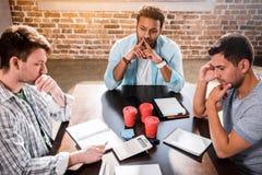 Geconcentreerde mensen die aan project op kleine bureauvergadering werken royalty-vrije stock afbeelding