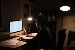 Geconcentreerde mensenzitting en het gebruiken van computer in donkere ruimte Stock Afbeeldingen