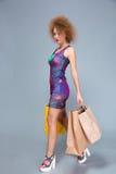 Geconcentreerde mooie krullende vrouw die met papieren zakken lopen Stock Foto