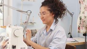Geconcentreerde naaister die aan een nieuwe orde werken die een naaimachine met behulp van Naaiende zaken stock videobeelden