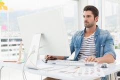 Geconcentreerde ontwerper die met becijferaar en computer werken Royalty-vrije Stock Afbeelding