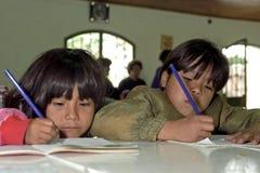 Geconcentreerde schrijvende meisjes in schoolgebouw stock foto's