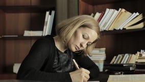 Geconcentreerde student die in de bibliotheek in universiteit bestuderen Vrouwelijke studentenzitting bij het bureau en het doen  stock video