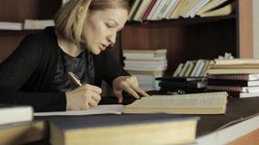 Geconcentreerde student die in de bibliotheek in universiteit bestuderen Vrouwelijke studentenzitting bij het bureau en het doen  stock videobeelden