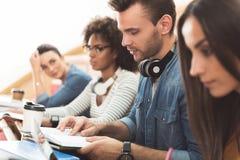 Geconcentreerde studenten die in auditieve ruimte bestuderen royalty-vrije stock afbeeldingen