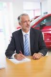 Geconcentreerde verkoper die op klembord bij zijn bureau schrijven Royalty-vrije Stock Fotografie
