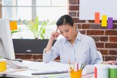 Geconcentreerde vrouw die bij bureau werken Stock Foto's