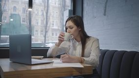 Geconcentreerde vrouw die haar laptop zitting gebruiken bij de lijst in koffie Meisjeszitting op de bank dichtbij venster het dri stock videobeelden