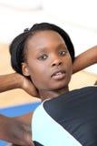 Geconcentreerde vrouw in gymnastiekuitrusting die zitten-UPS doet Stock Foto's