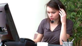 Geconcentreerde vrouw met hoofdtelefoon bij het werken bij een computer stock videobeelden