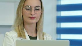 Geconcentreerde vrouwelijke arts in glazen die aan laptop bij ontvangstbureau werken stock videobeelden
