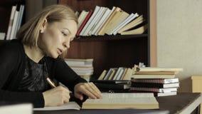 Geconcentreerde vrouwelijke student die met boeken in een bibliotheek in universitaire universiteit werken Vermoeide student die  stock videobeelden