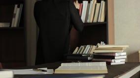 Geconcentreerde vrouwelijke student die met boeken in een bibliotheek in universitaire universiteit werken Vermoeide student die  stock video