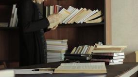 Geconcentreerde vrouwelijke student die met boeken in een bibliotheek in universitaire universiteit werken Vermoeide student die  stock footage