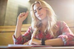 Geconcentreerde vrouwelijke student tijdens klasse stock foto's