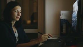 Geconcentreerde vrouwenontwerper die in bureau bij nacht werken die computer met grafiektablet en laptop met behulp van stock footage