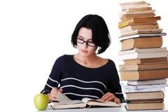 Geconcentreerde vrouwenzitting met stapel boeken Stock Fotografie