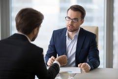 Geconcentreerde zakenliedenonderhandeling over bedrijfstrategieën in bureau royalty-vrije stock foto's