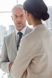 Geconcentreerde zakenman die aan vrouwelijke collega luisteren royalty-vrije stock afbeelding