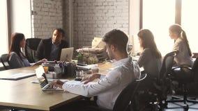 Geconcentreerde zakenman die met laptop zitting bij lijst in bureau werken stock videobeelden