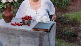 Gedächtnisse der älteren Personen Großmutter, die in einem Stuhl im Garten sitzt lizenzfreie stockbilder