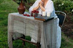Gedächtnisse der älteren Personen Großmutter, die in einem Stuhl im Garten sitzt auf dem Tisch gibt es zwei Gläser Milch, eine Pl stockbilder