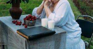 Gedächtnisse der älteren Personen Großmutter, die in einem Stuhl im Garten sitzt auf dem Tisch gibt es zwei Gläser Milch, eine Pl lizenzfreie stockbilder