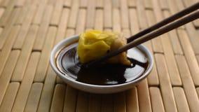 Gedämpfte chinesische Schweinefleischdim sum-Auswahl durch hölzerne Essstäbchen und das Eintauchen der Sojasoße auf Schale stock video