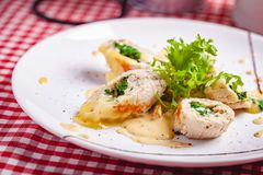 Gedämpfte Hühnerkoteletts angefüllt mit Spinat auf weißer Platte stockfotos