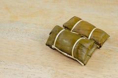 Gedämpfter klebriger Reis mit Banane auf hölzerner Tischplatte Lizenzfreie Stockfotos
