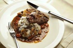 Gedünstete Rindfleischbacken mit Pilzen und gestampften purpurroten Kartoffeln stockfotos