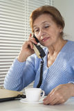 Ged female with a cup and a telephone Royalty Free Stock Image