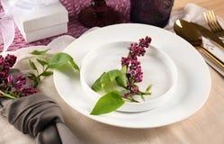 Gedeck in der lila Farbe und im Blumendekor Stockfotografie