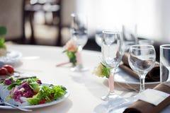 Gedeck im Restaurant Blumendekor auf den Gläsern, heiratend Stockfotografie