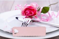 Gedeck mit einer einzelnen Rosarose Stockbild