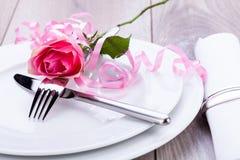 Gedeck mit einer einzelnen Rosarose Stockfoto